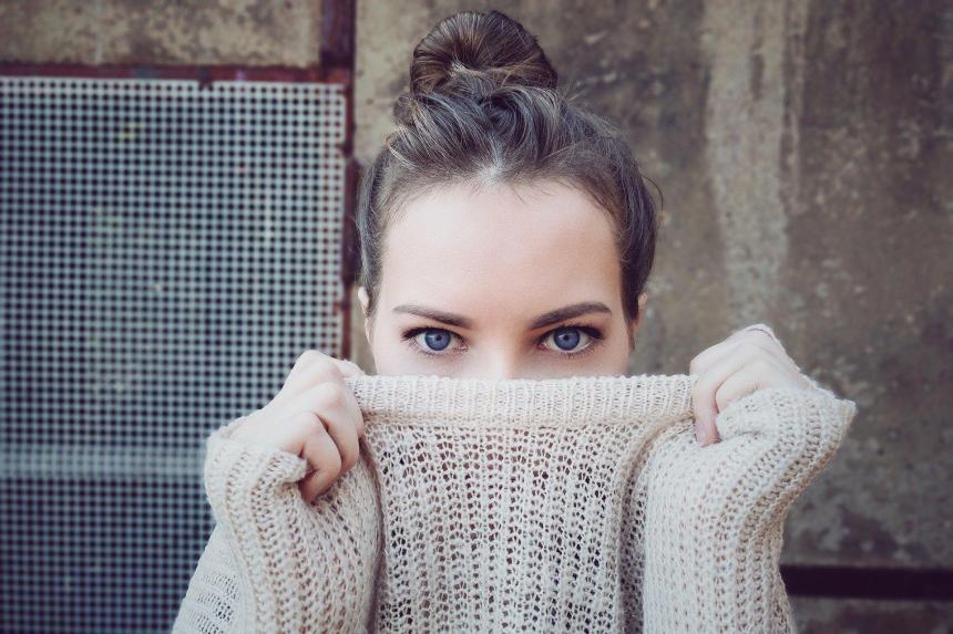 Flicka som döljer halva ansiktet med stickad tröja.